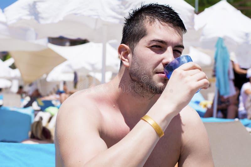 喝冷的金的年轻英俊的人在海滩 库存照片