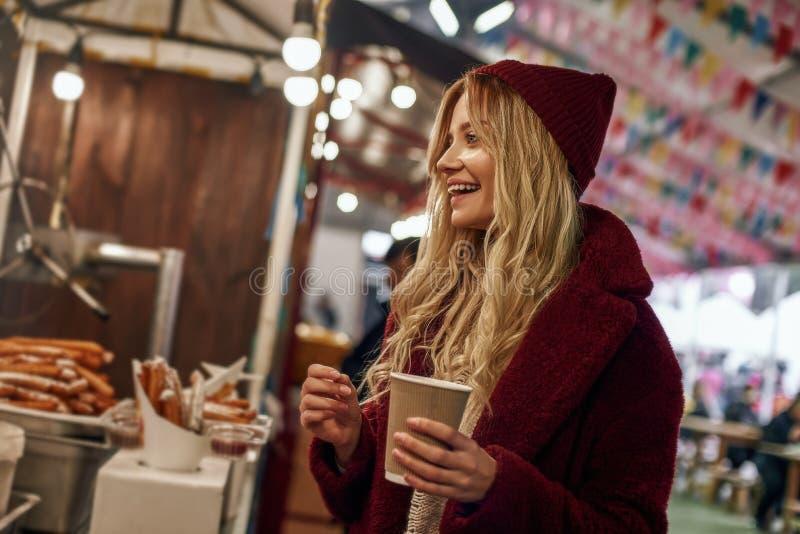 喝加香料的热葡萄酒的愉快的时髦的妇女在街道食物市场上 免版税库存照片