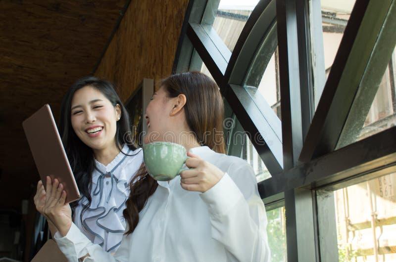 喝咖啡和使用一种数字式片剂的可爱的两个亚洲人女实业家 免版税库存图片