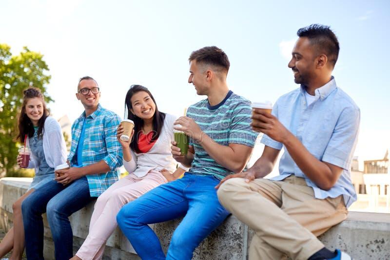喝咖啡和汁液的朋友谈话在城市 图库摄影