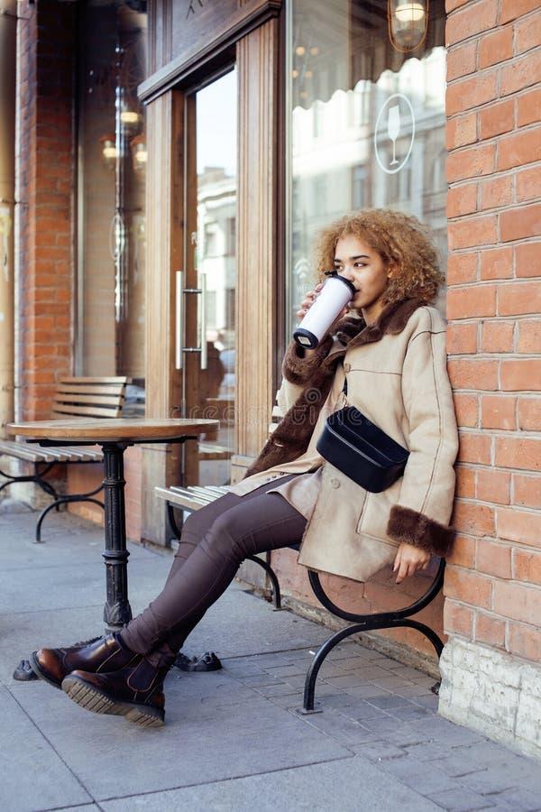 Download 喝咖啡外面在咖啡馆,现代女商人生活方式概念的年轻俏丽的非裔美国人的妇女 库存照片 - 图片 包括有 城市, 聚会所: 72369174