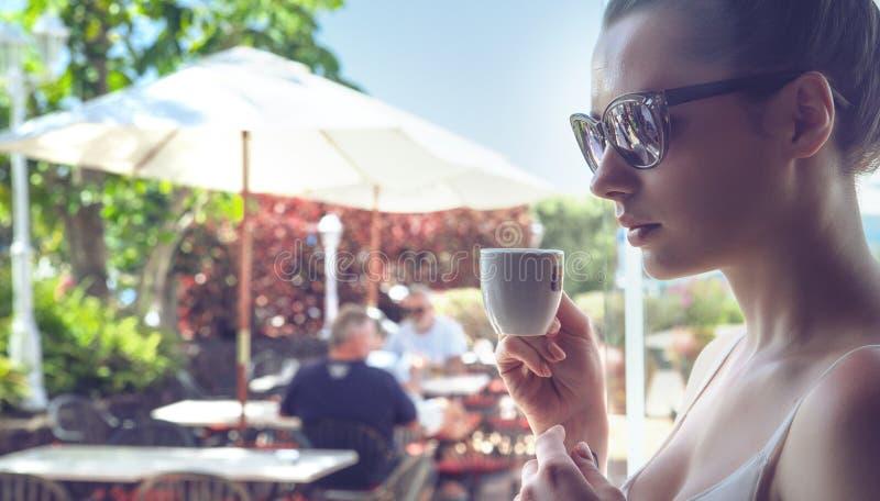 喝咖啡的一个可爱的夫人的画象 库存照片