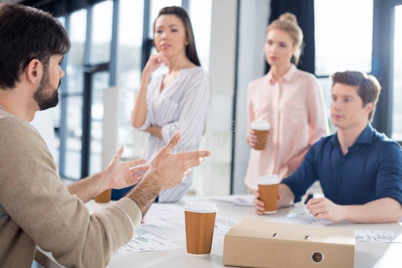 喝咖啡的专业买卖人,当谈论和群策群力在小企业办公室时 库存图片