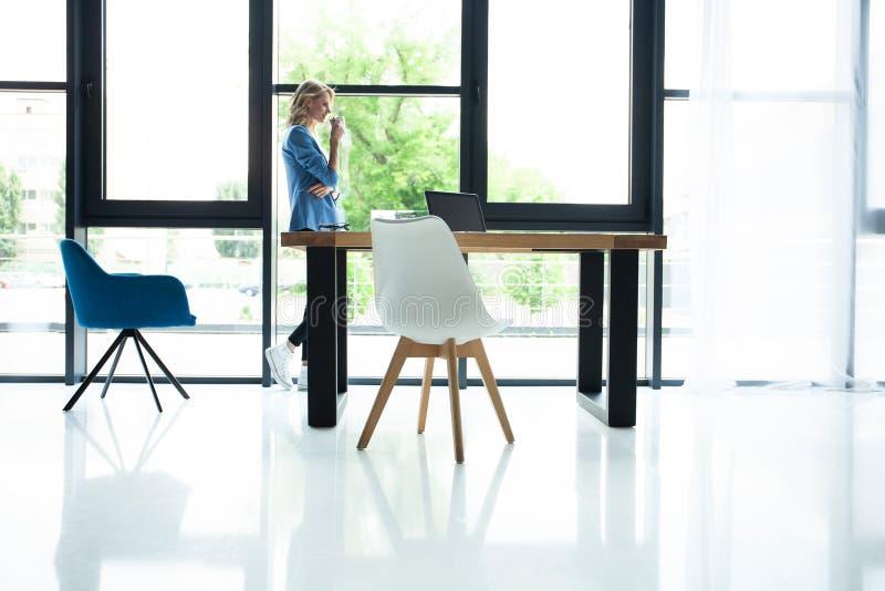 喝咖啡的可爱的女实业家,当站立在一个窗口在俯视城市时的办公室 图库摄影