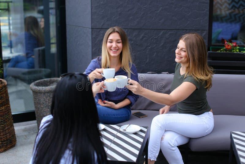 喝咖啡的快乐的妇女在咖啡馆和休息 图库摄影