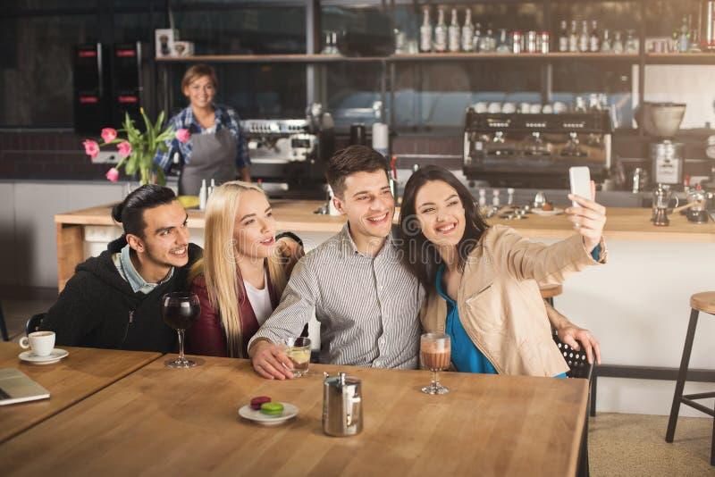 喝咖啡的愉快的年轻朋友在咖啡馆 免版税库存图片