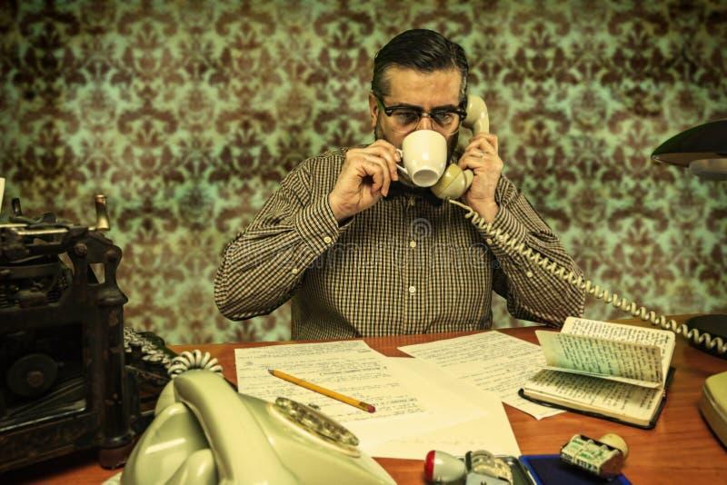 戴喝咖啡的眼镜的办工室职员,当谈话在时 免版税库存图片