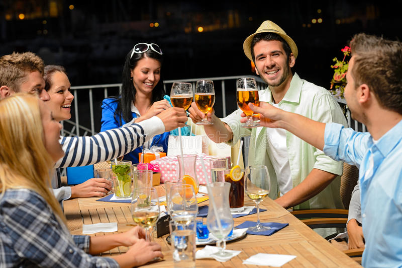 喝啤酒的小组年轻朋友户外 免版税库存图片