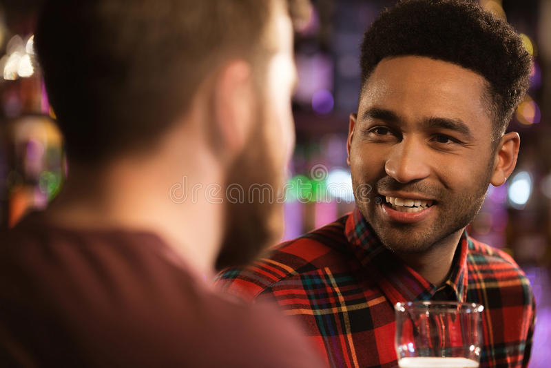 喝啤酒的两个愉快的男性朋友在酒吧 库存照片