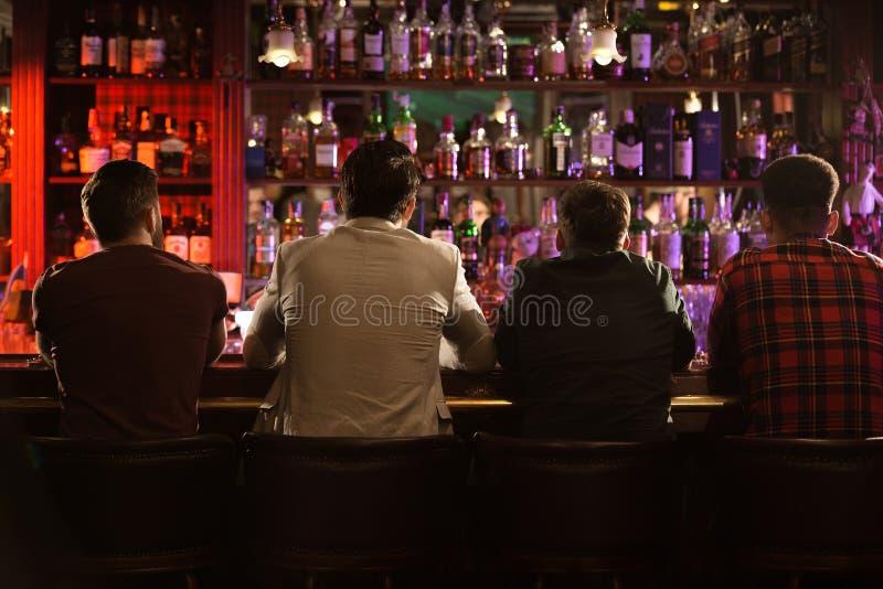 喝啤酒的后面观点的四个年轻人 免版税库存照片
