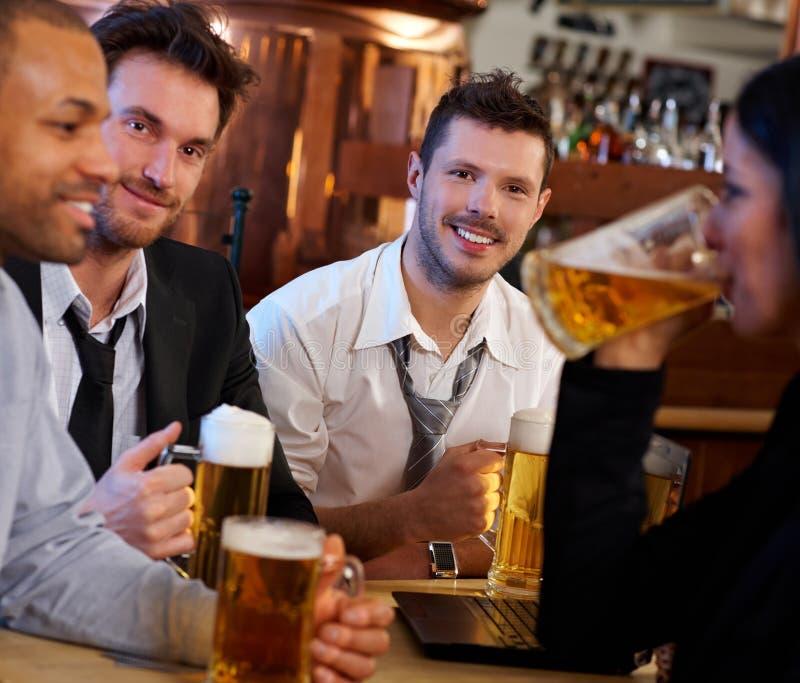 喝啤酒的小组朋友在客栈 库存照片