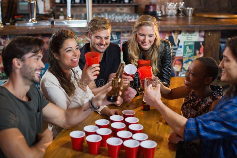 喝啤酒的愉快的朋友,当坐在酒吧时的一次性杯子附近 图库摄影