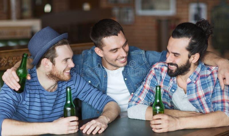 喝啤酒的愉快的男性朋友在酒吧或客栈 免版税库存图片