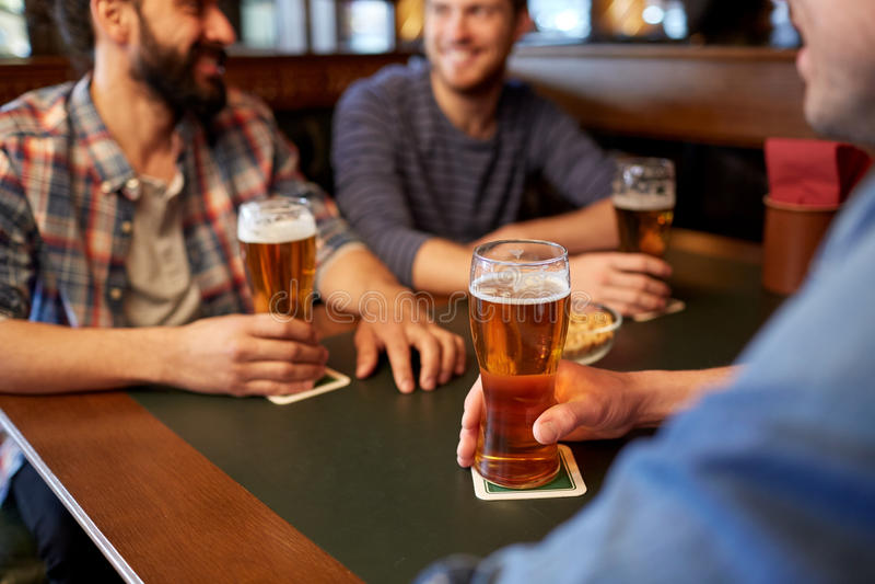 喝啤酒的愉快的男性朋友在酒吧或客栈 库存图片