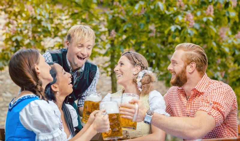 喝啤酒的朋友在啤酒庭院里 免版税库存照片