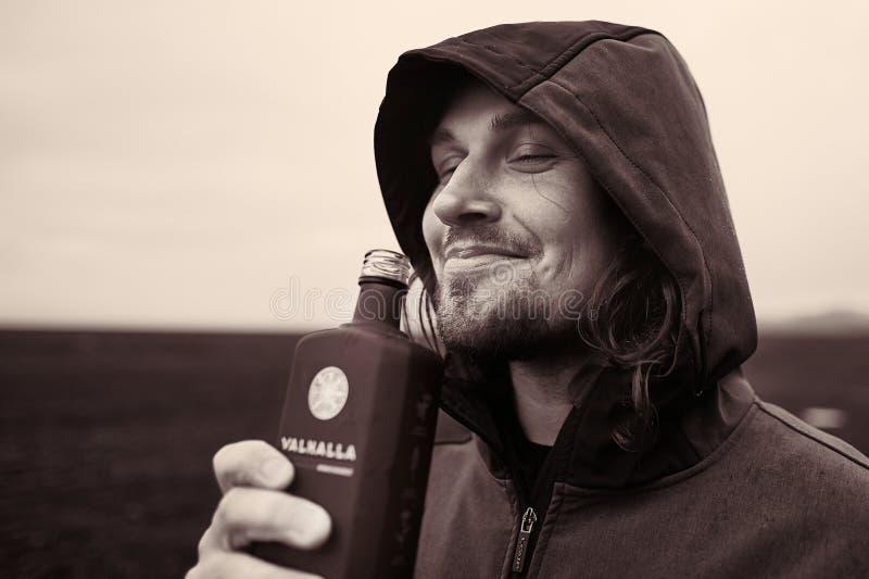 喝在冰岛的戴头巾人 库存图片