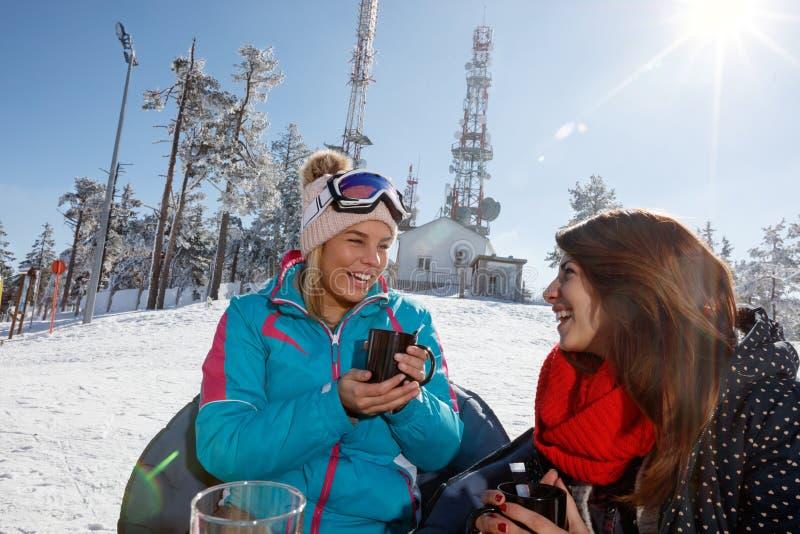 喝在咖啡馆的少妇茶在滑雪 免版税图库摄影