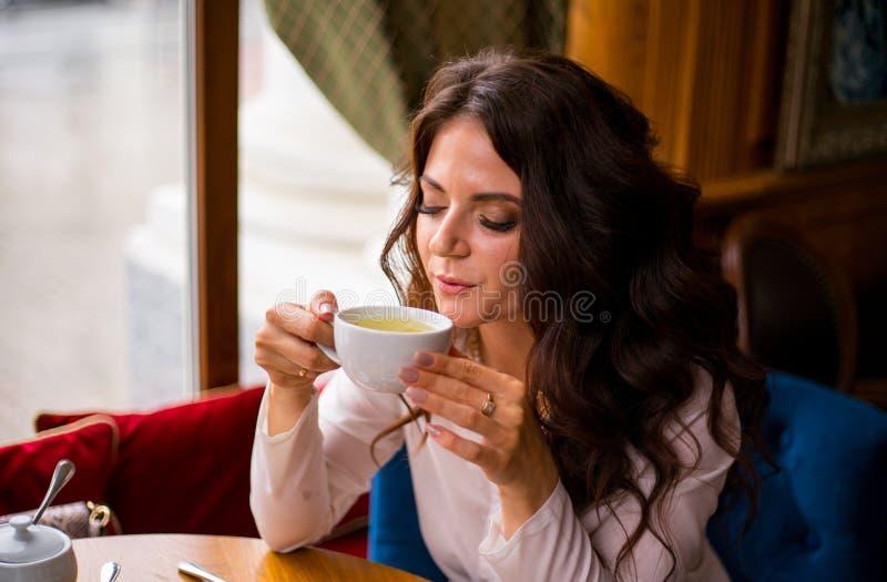 喝在城市咖啡馆的绿茶和神色的美丽的深色的妇女在照相机 库存图片