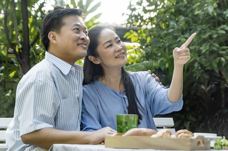 喝在庭院里的资深夫妇下午茶 库存图片