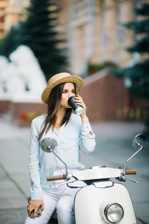 喝在意大利滑行车的年轻女实业家一份咖啡 站立在街道上的滑行车的妇女 库存照片