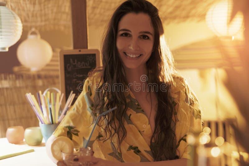 喝在日落的愉快的年轻女人 免版税图库摄影