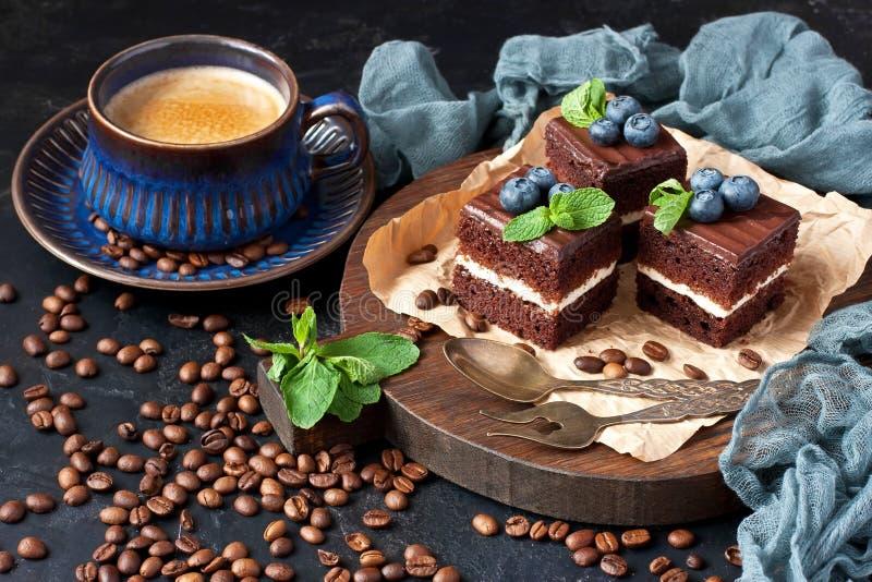 喝在杯子的热的咖啡有切片巧克力蛋糕的 图库摄影