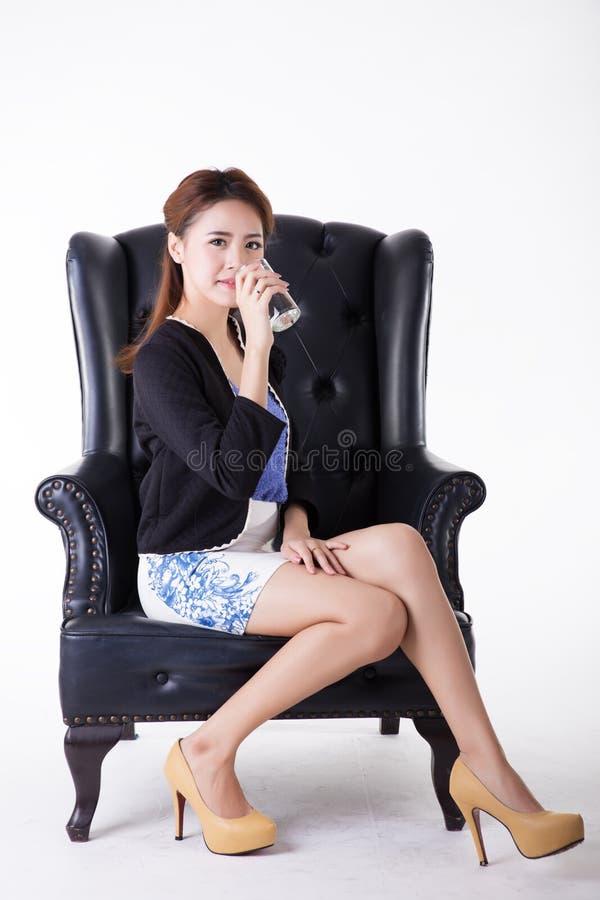 喝在椅子的女商人 免版税库存照片