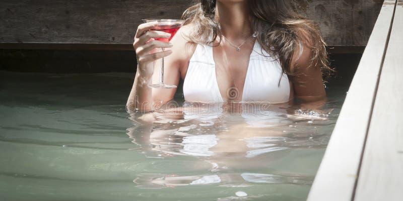 喝在池水的年轻可爱的女孩一个鸡尾酒 库存图片