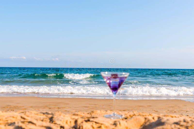 喝在波浪affectin的背景的马蒂尼鸡尾酒玻璃 免版税库存图片