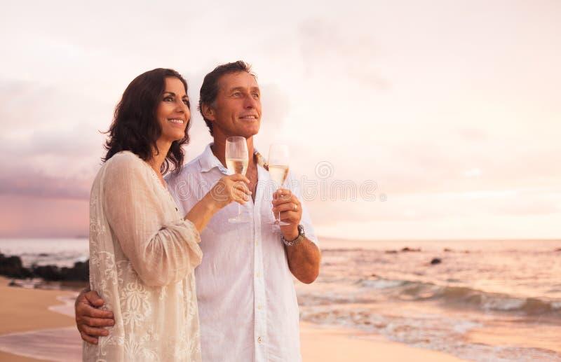 喝在海滩的浪漫夫妇香宾在日落 图库摄影