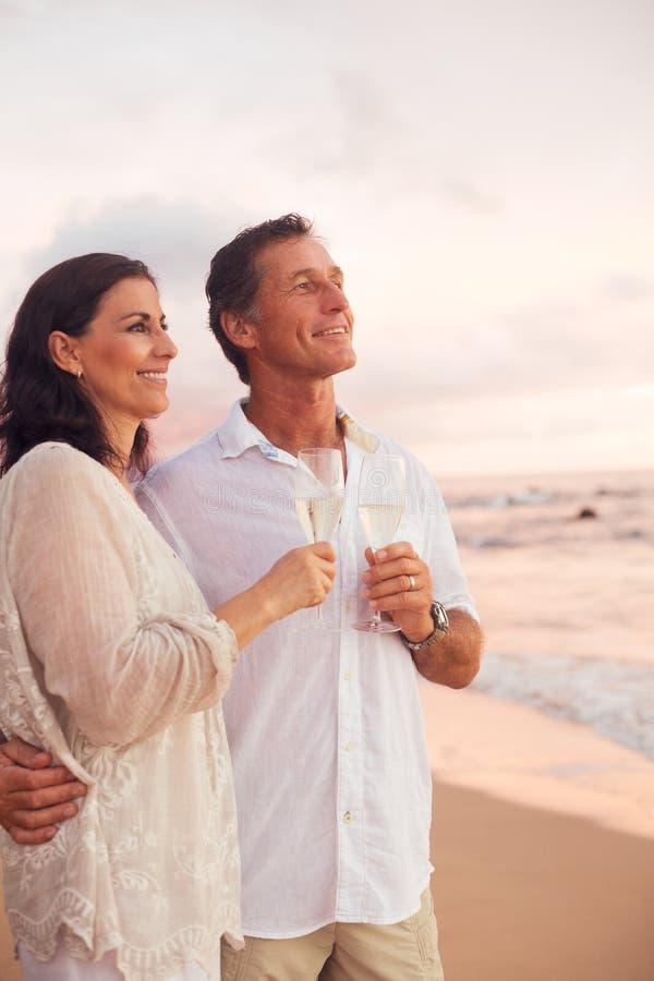 喝在海滩的浪漫夫妇香宾在日落 免版税库存照片