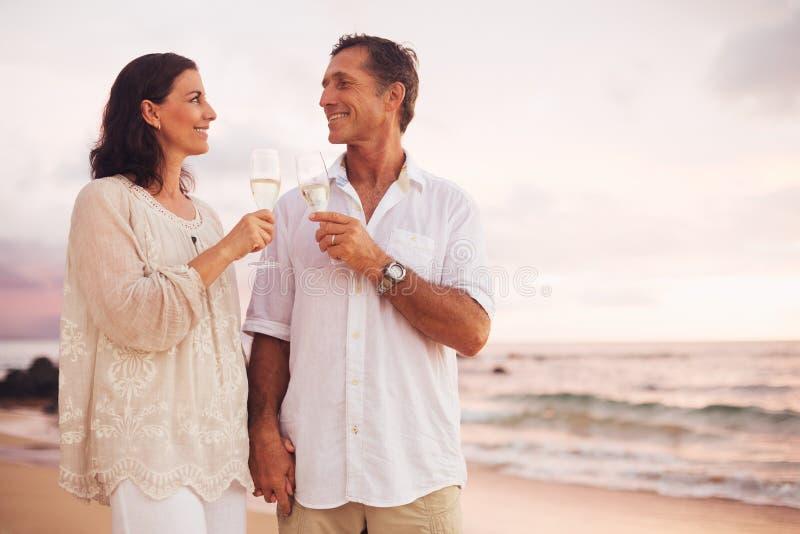喝在海滩的浪漫夫妇香宾在日落 免版税库存图片
