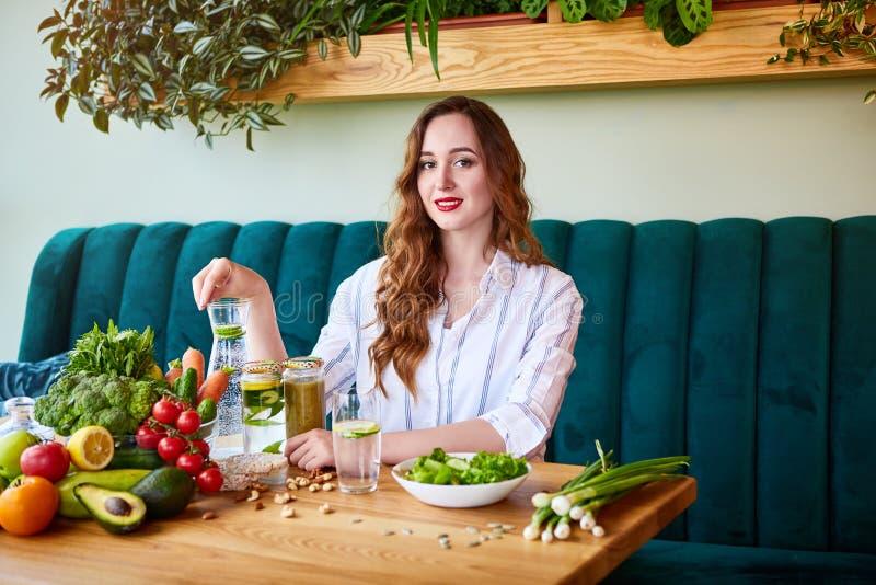 喝在美好的内部的年轻女人淡水与在背景的绿色花和新鲜的水果和蔬菜  免版税库存照片