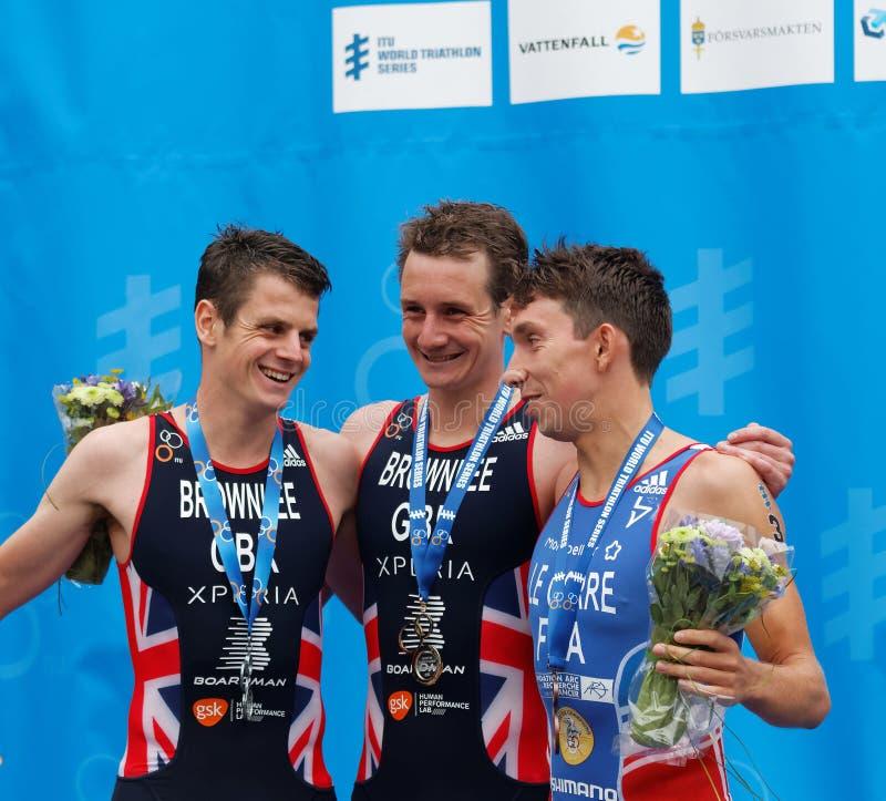 喝在podiu的微笑的奖章获得者triathletes香槟 免版税库存图片