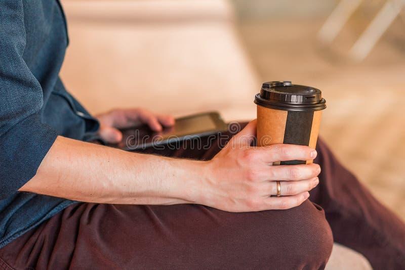 喝外带的咖啡的一个人的特写镜头在办公室 库存图片