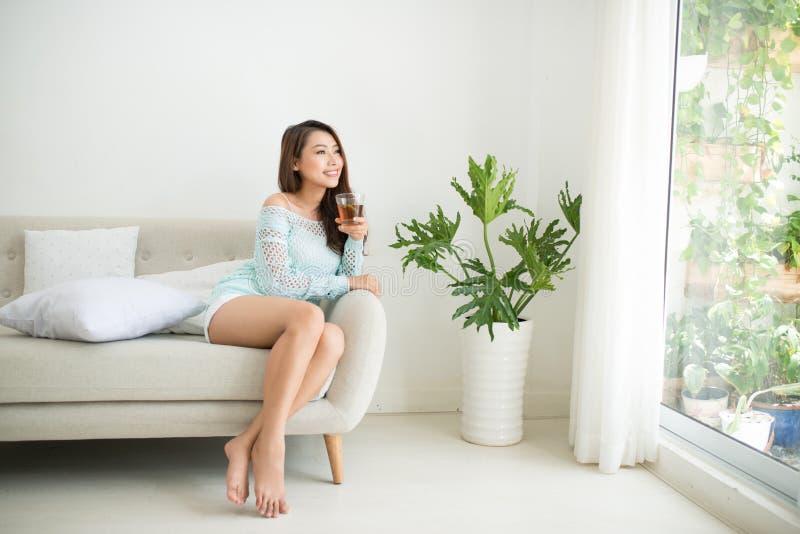 喝她的在brea的美丽的年轻亚裔妇女早晨茶 免版税图库摄影