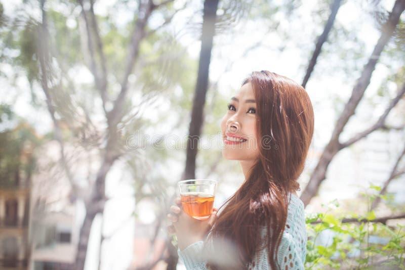 喝她的早晨茶的一名年轻亚裔妇女的画象 落r 免版税库存图片