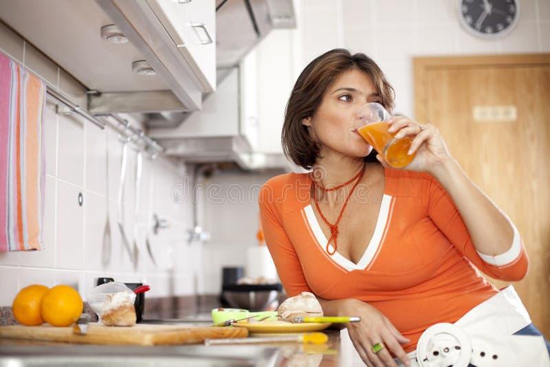 喝她的汁液桔子妇女 库存照片