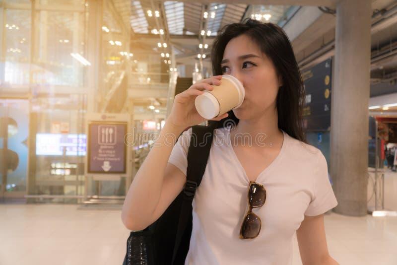 喝她的老妇人年轻人的背景美丽的后面城市咖啡 对奔忙旅行 库存照片