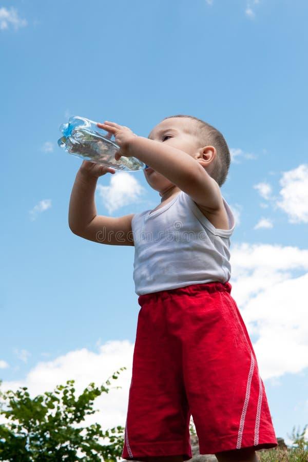 喝少许水的男孩 免版税库存照片
