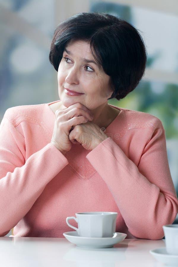 喝年长妇女的有吸引力的咖啡 免版税库存图片