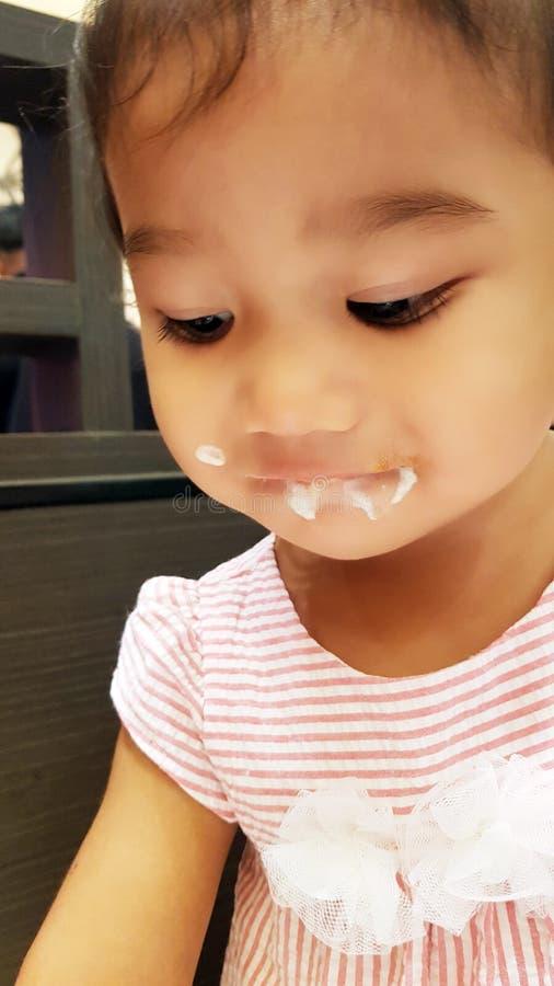 喝新近地被紧压的橙汁的逗人喜爱的滑稽的小女孩 免版税图库摄影