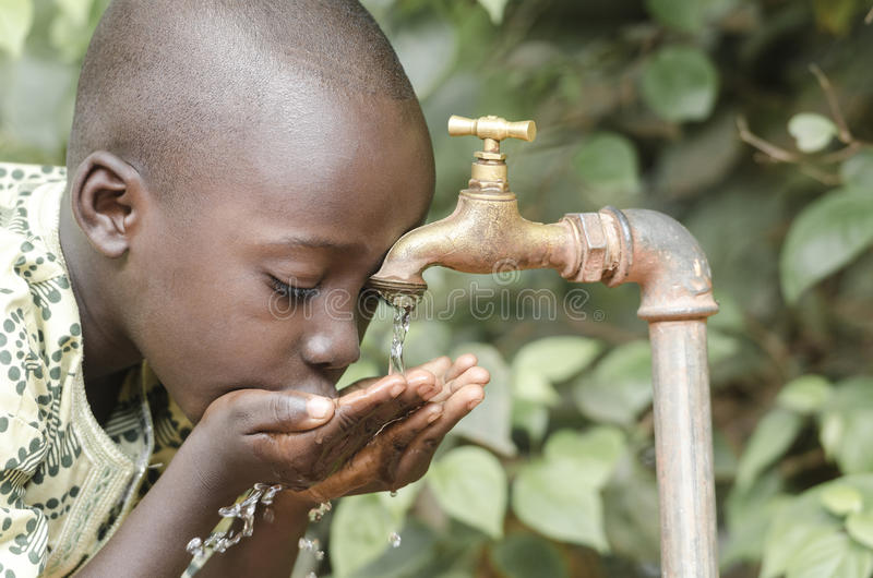 喝新鲜的净水的非洲黑人男孩 库存图片