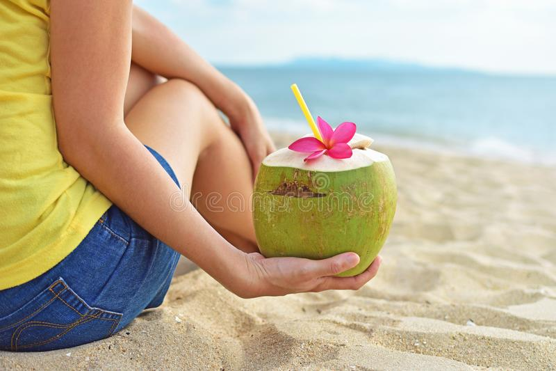 喝新鲜的椰子水的少妇 免版税库存照片
