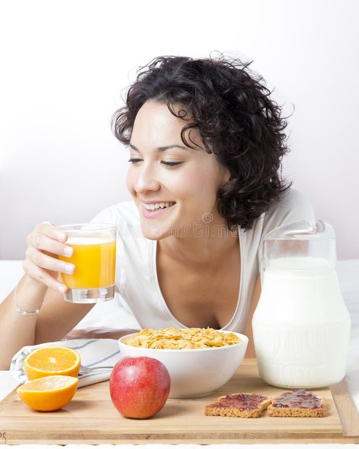 喝新鲜的橙汁在白色的健康早餐的妇女 免版税图库摄影