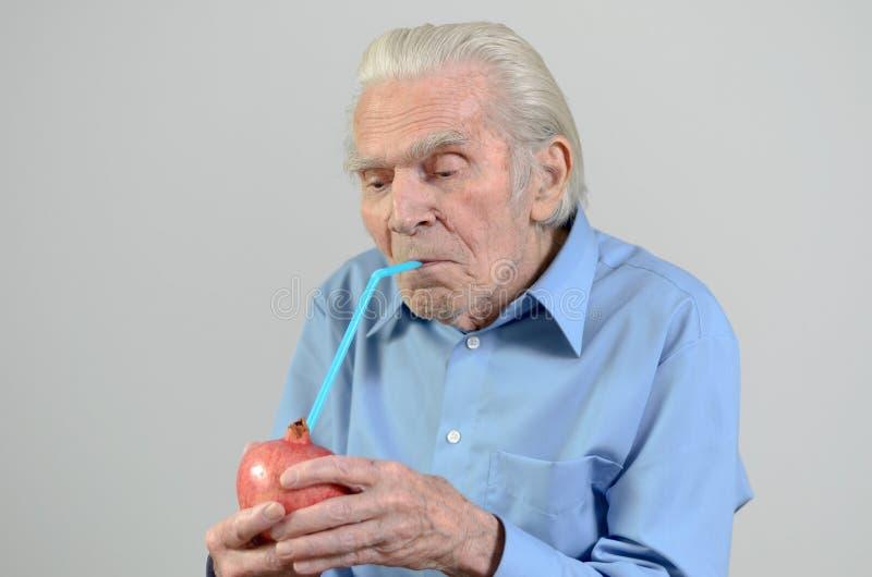 喝新鲜的石榴汁的老人 免版税库存照片