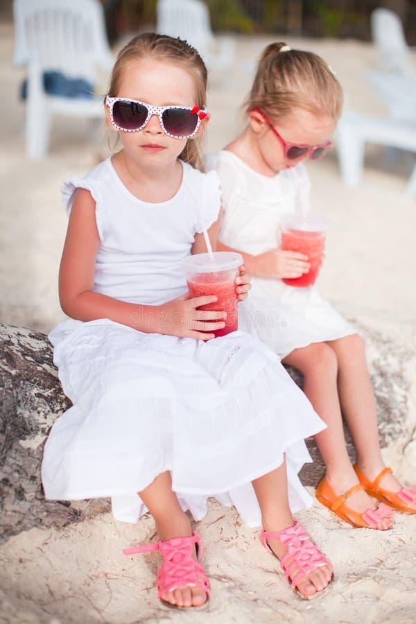 喝新鲜的西瓜的可爱的小女孩  免版税库存图片