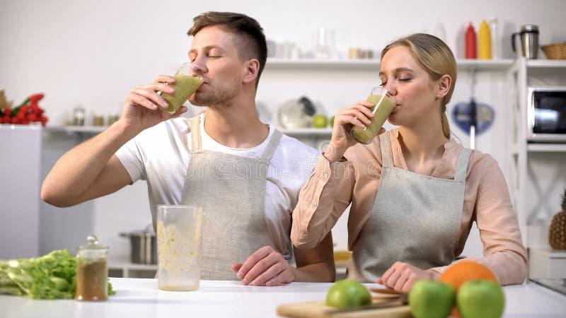 喝新鲜的spirulina圆滑的人、维生素和矿物的年轻健康夫妇 库存照片