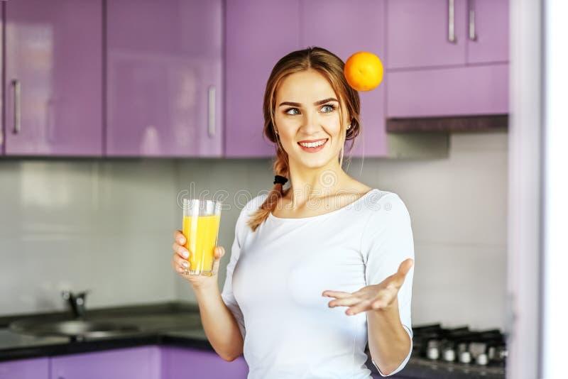 喝早餐A妇女Th的年轻愉快的女孩橙汁 免版税库存照片