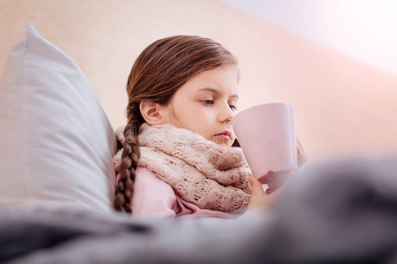 喝有用的无味的茶的不快乐的女孩 库存图片